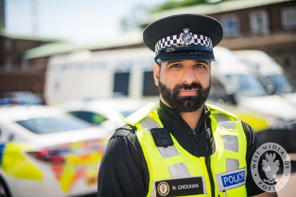 Special Inspector Navdeep Chouhan outside in front of some police cars and vans